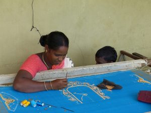 Sudgadhi embroiders a saaree while her son sits next to her